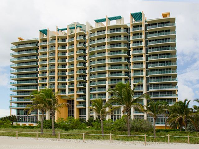 Beach front multi story condo building with large balconies and landscaping.
