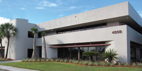 Gray concrete office building with palm trees and grass.